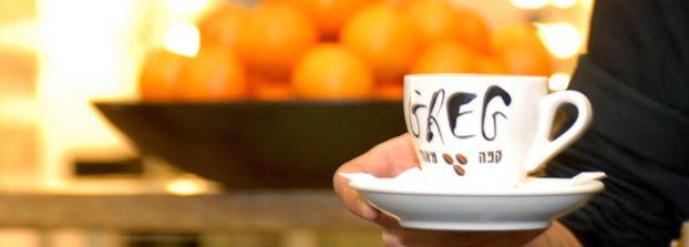 ספל קפה שכתוב עליו GREG. סגול עשוי מפולי קפה ב־E