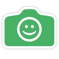 """שלט """"מותר לצלם"""". השלט בצורת מצלמה, ברקע ירוק ועם פרצוף מחייך באמצע."""