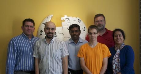 צוות התמיכה הלשונית, צילום קבוצתי על רקע סמל ויקיפדיה במשרדי קרן ויקימדיה בסן פרנסיסקו